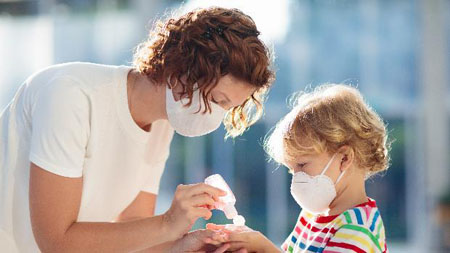 Madre enseñando a su hijo a desinfectarse las manos para eliminar el Coronavirus Covid-19.