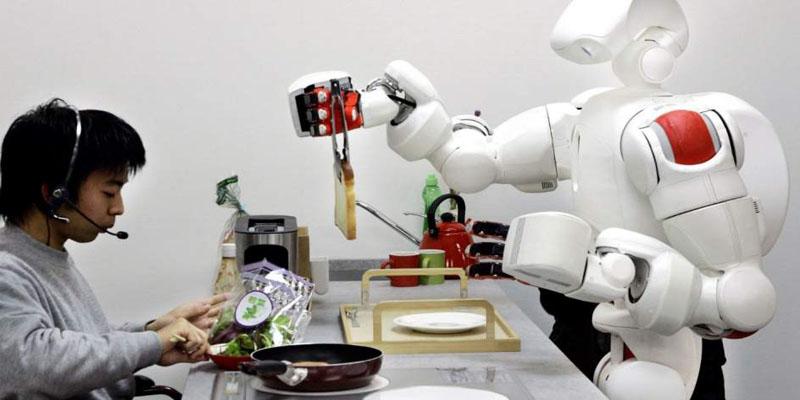 Robot y humano interactuando en una mesa de cocina.